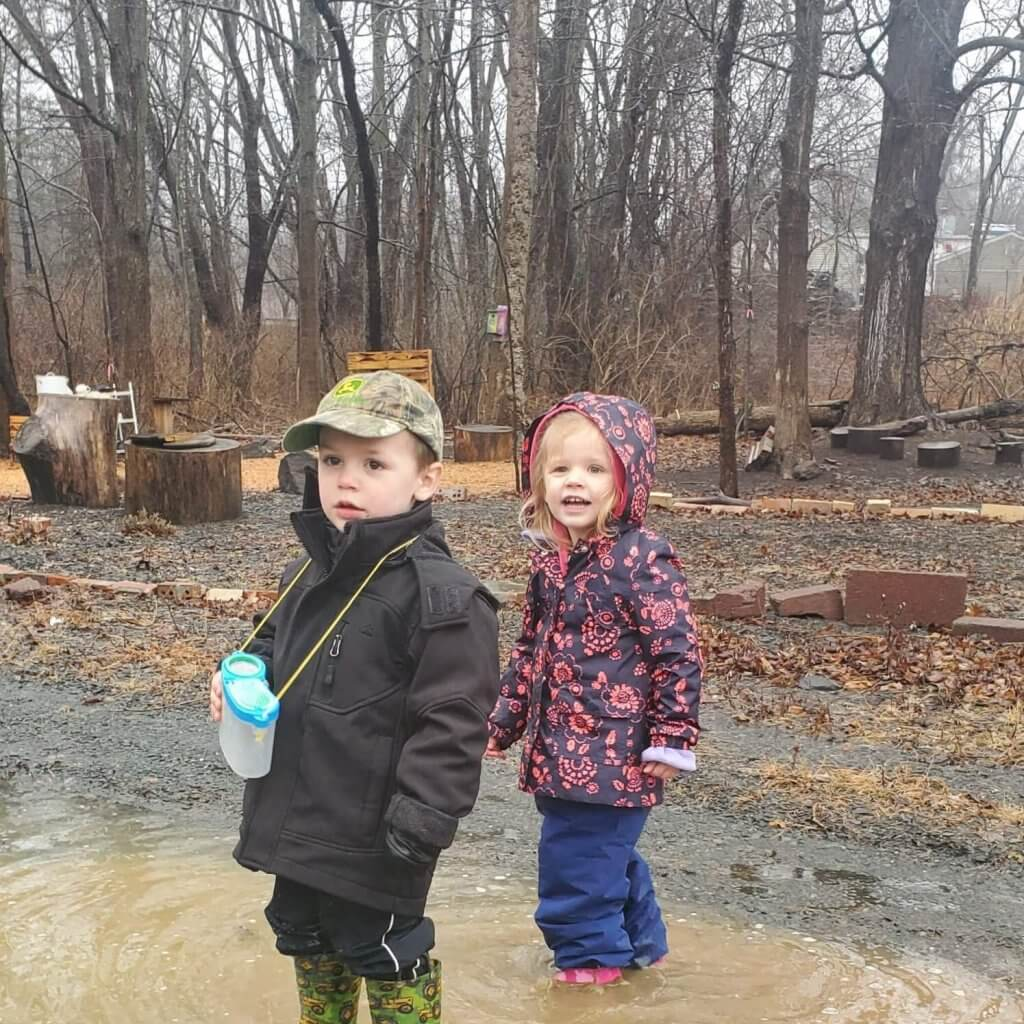 children in forest puddle