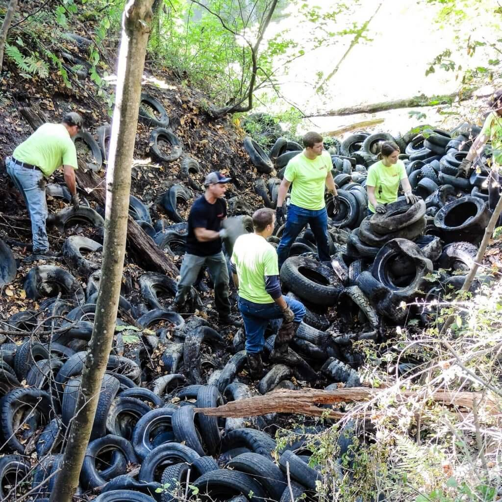 volunteers removing pile of tires